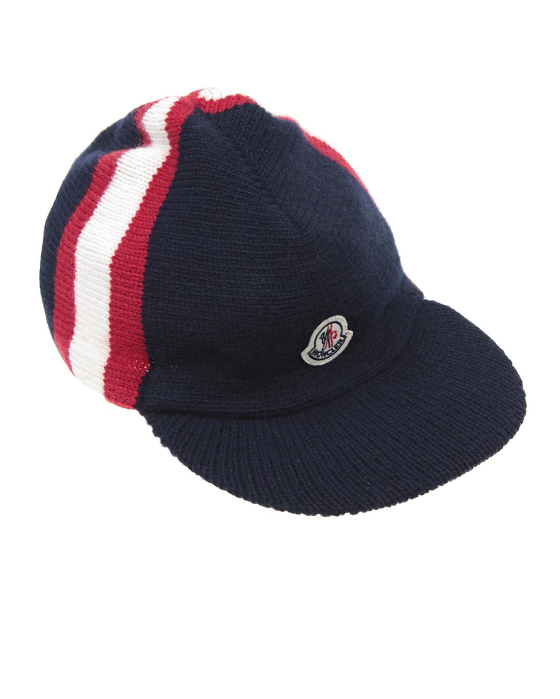 Шапка MonclerШапки<br>Темно-синяя шапка MONCLER с полосами в фирменных цветах бренда. Модель с плотным козырьком хорошо держит форму. Спереди нашивка с логотипом бренда.