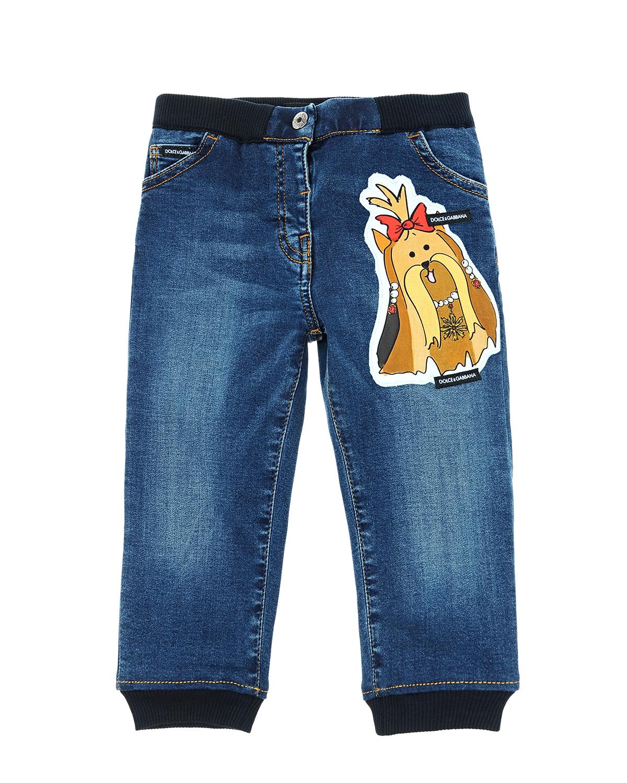 Джинсовые брюки с аппликациями Dolce&GabbanaДжинсы<br>Синие джинсовые брюки  DolceGabbana из стрейч-хлопка с эффектом потертостей. Модель с характерными для джинсов пятью карманами, поясом на резинке и манжетами по низу брюк. Пояс и манжеты черного цвета. Джинсы декорированы аппликациями с изображением собак в коронах.