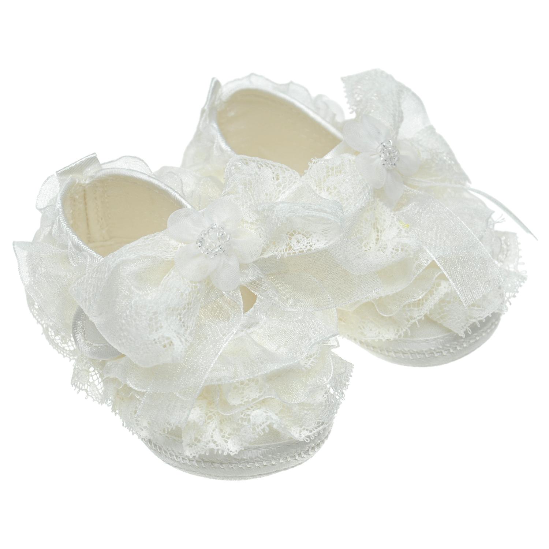 Белые пинетки с кружевной отделкой Baby ChickПинетки<br>Белые текстильные пинетки для Baby Chick. Модель декорирована кружевными рюшами, объемным текстильным бантом с цветком и кристаллами.