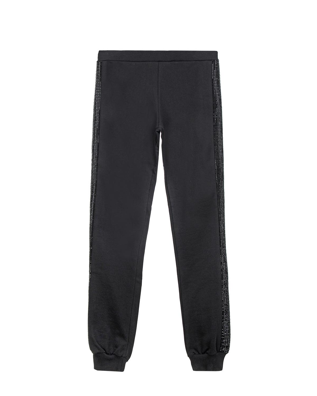 Брюки спортивные Philipp PleinСпортивная одежда<br>Черные спортивные брюки PHILIPP PLEIN с заниженной посадкой. Пояс на резинке обеспечивает удобную посадку по фигуре. Низ брюк отделан эластичными манжетами в тон. По боковым швам брюки отделаны тесьмой со стразами.
