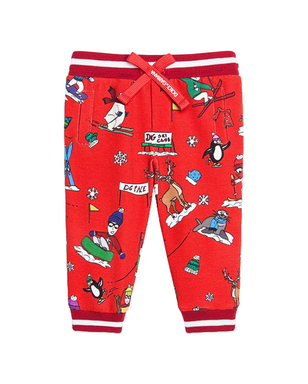 Красные спортивные брюкиСпортивная одежда<br>Красные спортивные брюки DolceGabbana из шерстяного трикотажа. Модель с эластичным поясом с лентой, двумя боковыми карманами и манжетами. Манжеты и пояс в красно-белую полоску. Брюки декорированы сплошным принтом с изображением дизайнеров-лыжников.