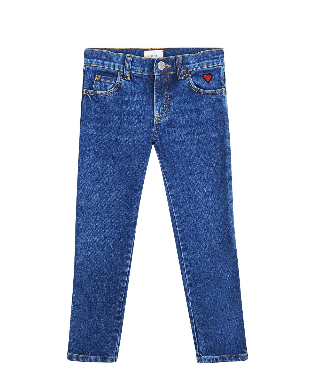 Яркие синие джинсы с сердечкомДжинсы<br>Джинсы Gucci из плотного денима насыщенного голубого цвета. Модель зауженного кроя со средней посадкой и классическим поясом застегивается на молнию и пуговицу. Спереди на кармане яркий патч красного цвета в форме сердечка. Сзади на поясе кожаная нашивка с логотипом бренда.