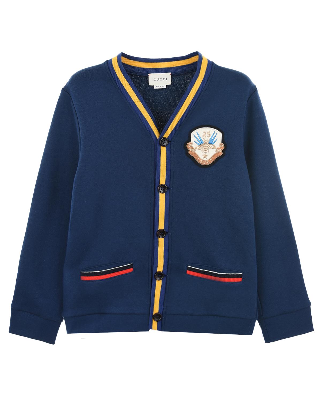 Синий кардиган с контрастной полоскойКардиганы, Кофты<br>Синий кардиган итальянского бренда Gucci прямого кроя для повседневных образов в стиле preppy. Свободная модель с длинными рукавами и эластичными манжетами. V-образный вырез и планка с пуговицами оформлены ярко-желтой полоской. Прорезные горизонтальные карманы с контрастной эластичной вставкой трех цветов. Полочка украшена гербовым патчем с пчелой.