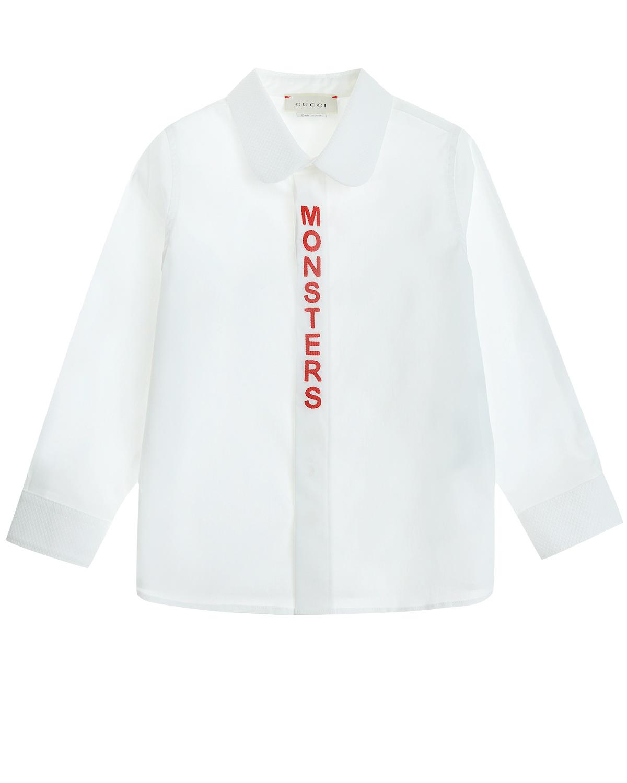 Рубашка GUCCIБлузы, Рубашки, Туники<br>Белая рубашка GUCCI с длинными рукавами из хлопка с добавлением эластана. Отложной воротник с закругленными краями из ткани с «вафельной» фактурой. Планка застежки декорирована контрастной вышивкой-надписью.