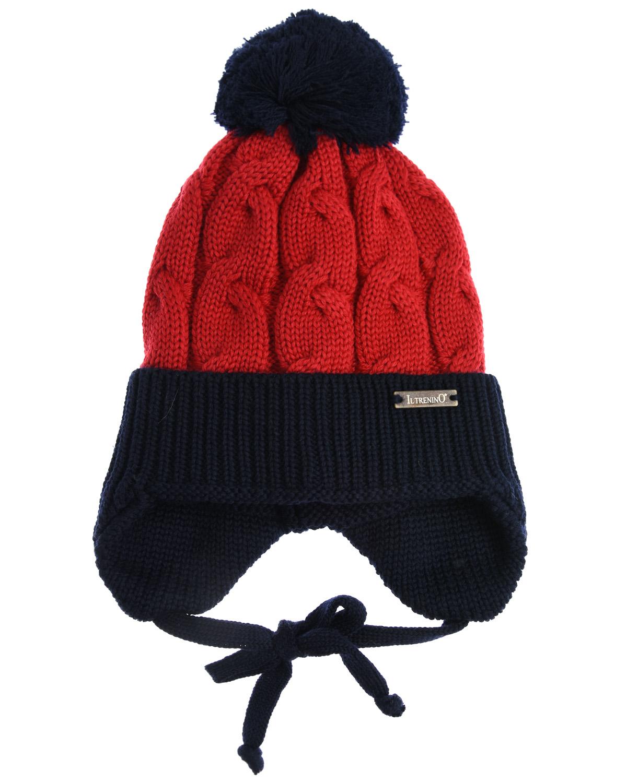 Шапка с помпономШапки<br>Красно-синяя шерстяная шапка Il Trenino. Модель с закрытыми ушками, завязками и флисовой подкладкой. Шапка декорирована шерстяным помпоном.