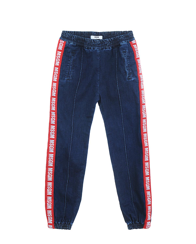 Джинсы с лампасами MSGMДжинсы<br>Синие джинсы MSGM из стрейч-хлопка. Модель с поясом на резинке, двумя боковыми карманами, манжетами и стрелками. Джинсы декорированы красными лампасами с логотипом.