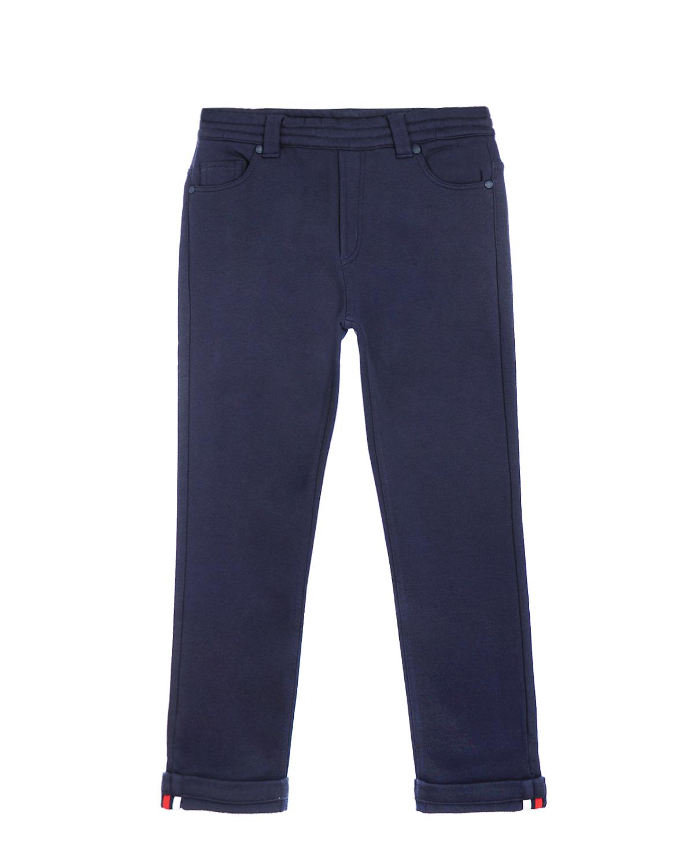 Брюки спортивные MonclerСпортивная одежда<br>Синие спортивные брюки MONCLER из натурального хлопка. Верх с 5-ю карманами  и имитацией застежки спереди. Удобный пояс на резинке не стесняет движения. Низ брюк выполнен с отворотами и отделкой в цветах бренда.