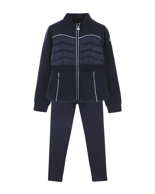 Спортивный костюм из двух деталей MonclerСпортивная одежда<br>Спортивный костюм Moncler состоит из толстовки и брюк, сшитых из плотного трикотажа. Толстовка приталенного кроя с высоким воротником застегивается на молнию. Модель дополнена утепленной вставкой из стеганого нейлона, с широкой эластичной лентой по низу. Спереди расположены два прорезных кармана на молнии. Левый рукав украшен патчем с логотипом. Детали изделия отделаны тонким белым кантом. Посадка брюк на талии регулируется широкой резинкой на поясе.