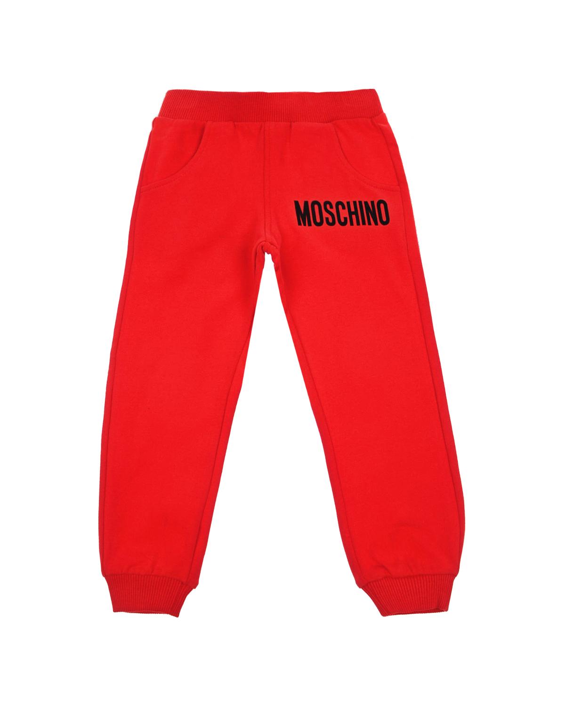 Красные спортивные брюкиСпортивная одежда<br>Красные спортивные брюки Moschino из хлопкового трикотажа. Модель с эластичным поясом, двумя боковыми карманами и манжетами. Брюки декорированы принтом с изображением логотипа.