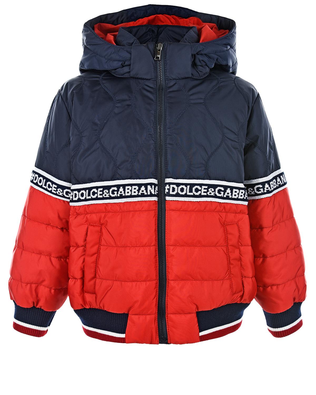 Двухцветная куртка-бомбер с декоративной лентойЗимние куртки. Пуховики<br>Двухцветная куртка-бомбер DolceGabbana сшита из водонепроницаемого нейлона с теплым наполнителем «пух-перо». Модель с капюшоном украшена широкой сине-белой лентой с логотипом. Темно-синий верх прошит волнообразной строчкой, ярко-красный низ — горизонтальной. Высокий воротник и эластичная отделка подола и манжет гарантируют отличную защиту от ветра. Два прорезных кармана, как и само изделие, застегиваются на молнию.